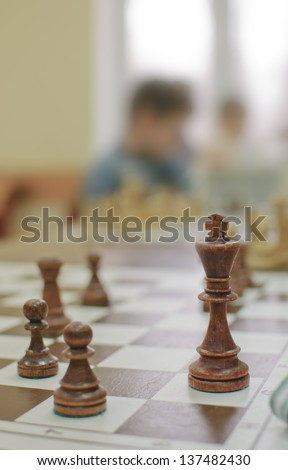 Wooden chess pieces on the Board on the background of the children Silhouettes   - stock photo