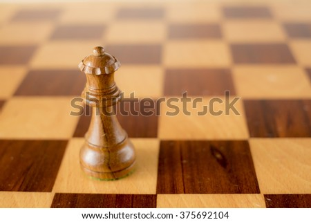 wooden chess set, black queen on board