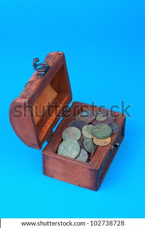 Wooden chest with coins inside isolated on blue - stock photo