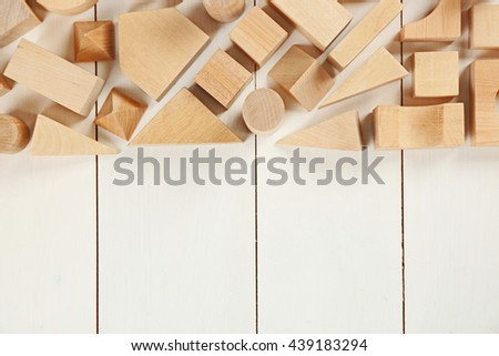 Wooden children's cubes on white wooden background - stock photo