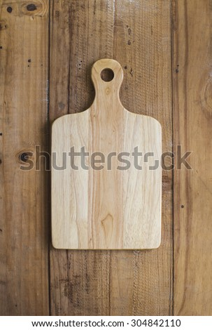 Wooden chop board on rustic wooden table top. Top view. - stock photo