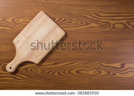 Wooden chop board on wooden table top. Top view. - stock photo