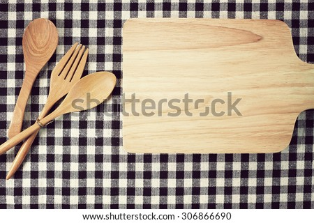 Wooden chopping block, fork and spoon on tablecloth background. Top view. Toned image. - stock photo