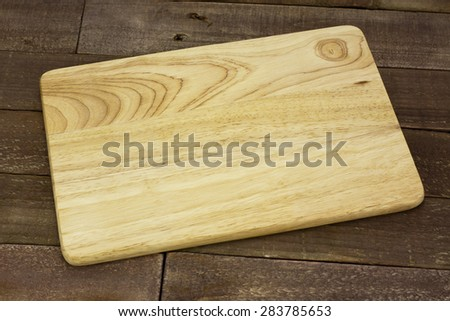 Wooden chopping board on an old table