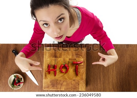 wooden chopping board with chillis making the word hot, taken from a birds eye view from above looking down at a woman - stock photo