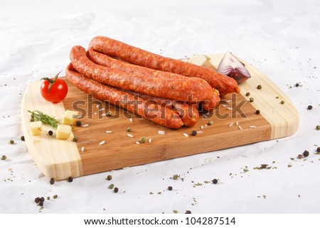 wooden chopping board with sausages and spices - stock photo