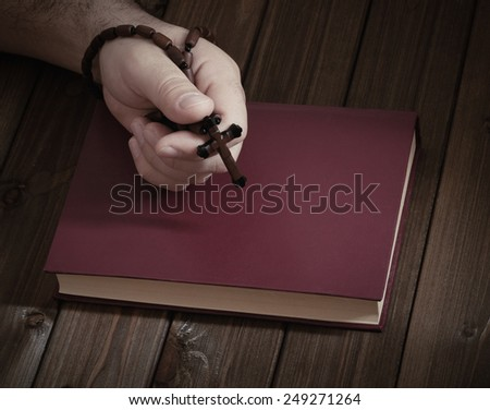 wooden Christian cross in his hand on the Bible during prayer. - stock photo