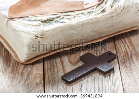 Wooden Christian cross on bible. Religious symbols concept.