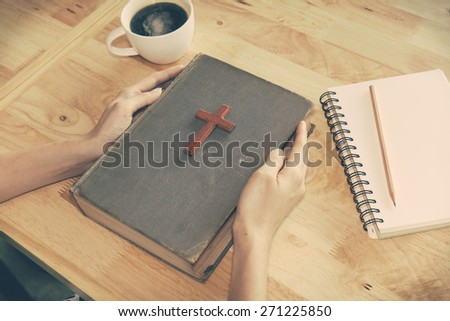 wooden Christian cross on the Bible during prayer. - stock photo