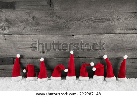 Wooden christmas background with red santa hats for a festive frame or card. - stock photo