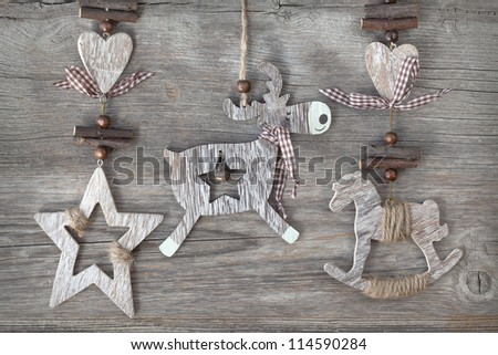 Wooden christmas deer,star and rocking horse on wooden background - stock photo