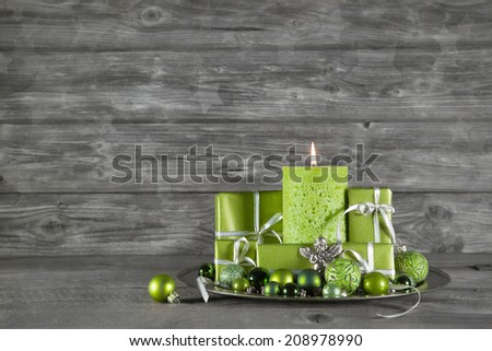 Wooden christmas or advent background with green decoration, candle and presents. - stock photo