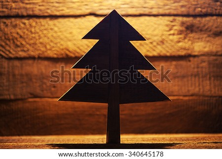 Wooden christmas tree on natural background with backlight - stock photo