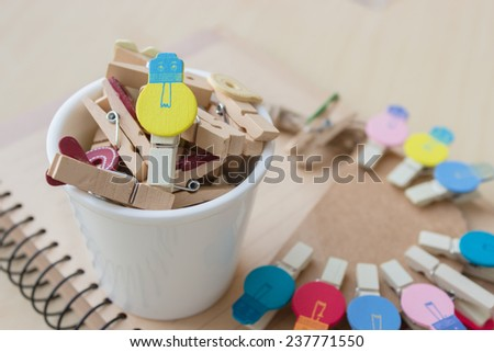 wooden clip set for paper clip and mini cup put on the notebook, concept of new idea. focus to the yellow wooden clip and warm light