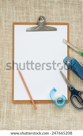 wooden clipboard on  sackcloth background, with regular white blank paper and office stationery. - stock photo