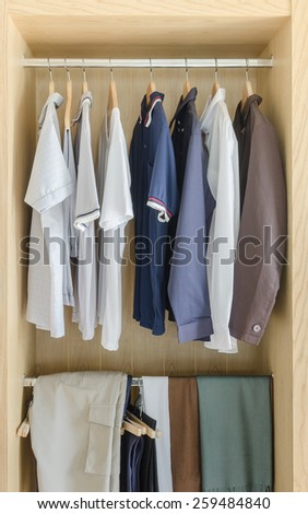 wooden closet with clothes hanging at home