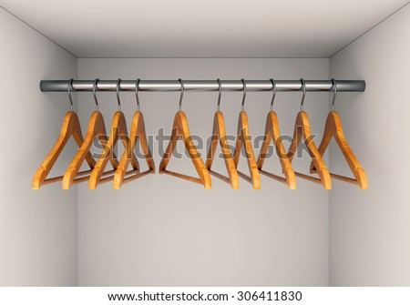 Wooden cloth hangers on clothes rail in wardrobe