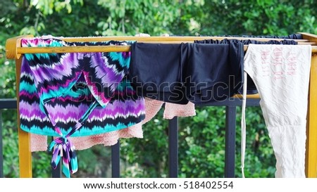 wooden cloth rack with swim suit and bikini hang on it