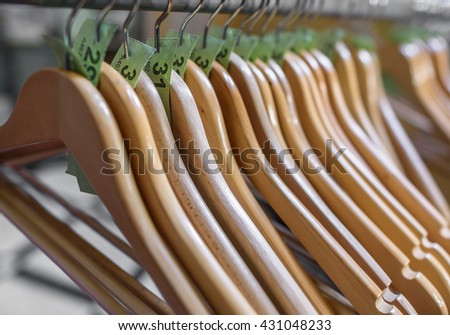 Wooden clothes hangers on a rail with numbered tickets.