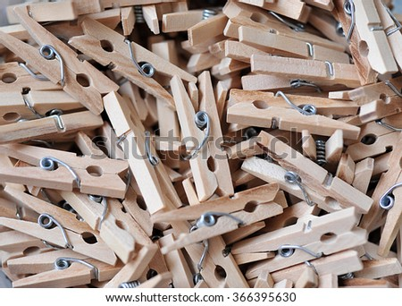 wooden clothespins piled on the floor and dark wood. - stock photo