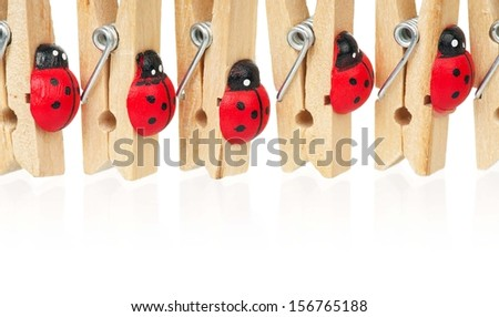 Wooden clothespins with ladybirds rowed over white background
