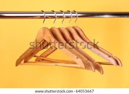 wooden coat hangers on a clothes rail - stock photo