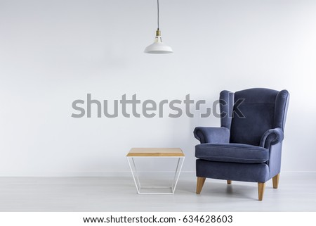 Wooden coffee table and blue armchair in simple room