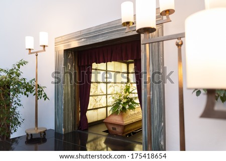 Wooden coffin with funeral flowers in crematorium - stock photo