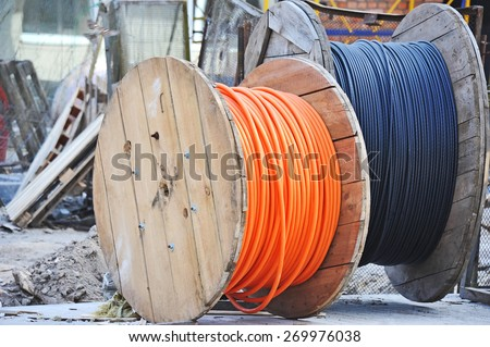 Wooden coil of electric cable on construction site - stock photo