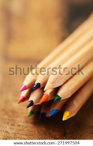 Wooden colorful pencils on wooden table - stock photo