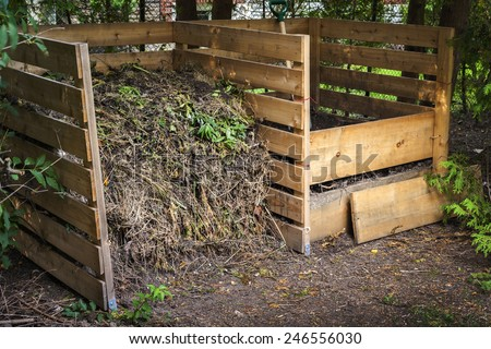 Wooden compost boxes with composted soil and yard waste for garden composting in backyard - stock photo