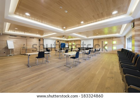 wooden conference room with presentation wall and projector - stock photo