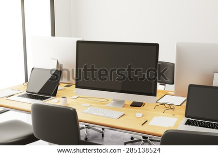 Wooden conference table with office accessories and computers
