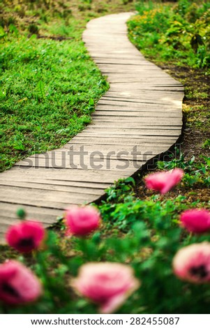 Wooden convoluted path in a spring garden in the morning