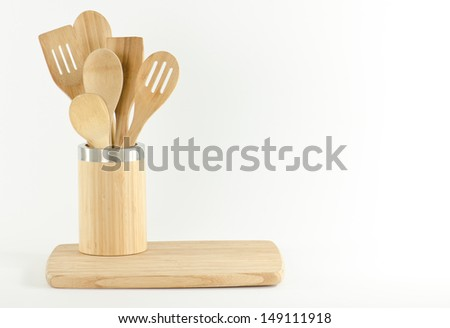 wooden cooking utensils in a bamboo holder on a cutting board