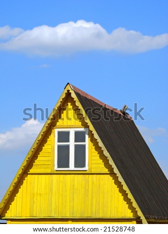 wooden cottage fragment against blue sky with light clouds