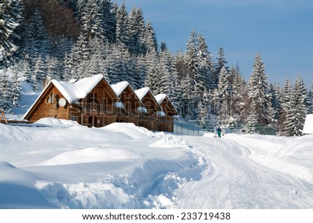 Wooden cottage in snowy mountains near the forest, snow at roof, skiers