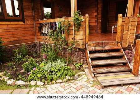 wooden cottage log house porch with steps and flowerbed close up photo - stock photo
