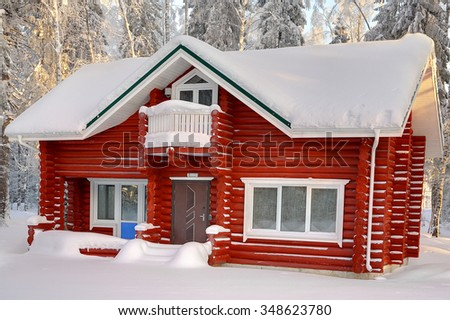Wooden cottage of red painted logs, with snow-covered roof on background of snowy winter forest in daytime. - stock photo