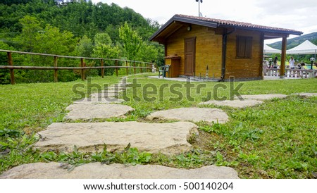 wooden cottage on green field