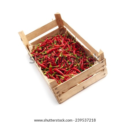 Wooden crate box full of chilies on a white background. - stock photo