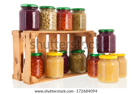 Wooden crate full with glass pots preserved vegetables - stock photo