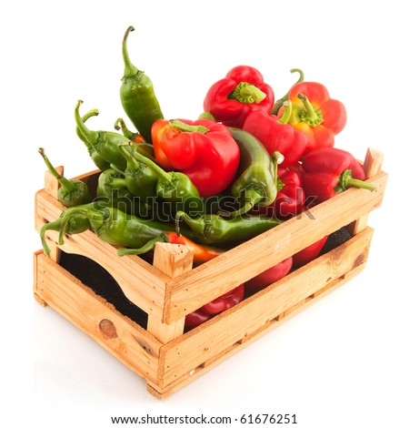 Wooden crate full with mixed Paprika isolated over white