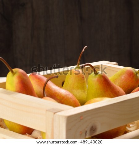 Wooden crate with organic pears on the white table