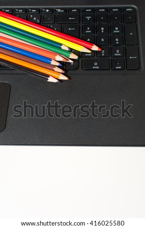 Wooden crayons on black computer keyboard.