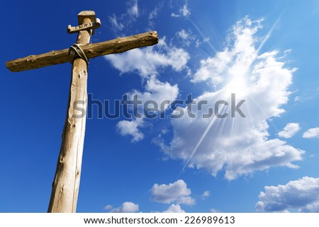 Wooden Cross Against a Blue Sky / Old wooden cross (trunks of trees) tied with ropes with blue sky, clouds and sunlight