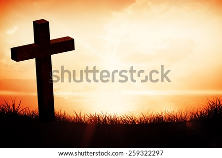 Wooden cross against orange sunrise