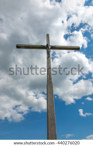 wooden cross against partly cloudy sky