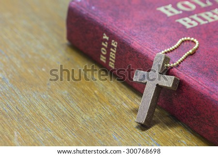 wooden  cross and red holy bible on wooden background - stock photo