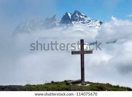 wooden cross in the clouds on a background of snowy peaks in the Swiss Alps - stock photo